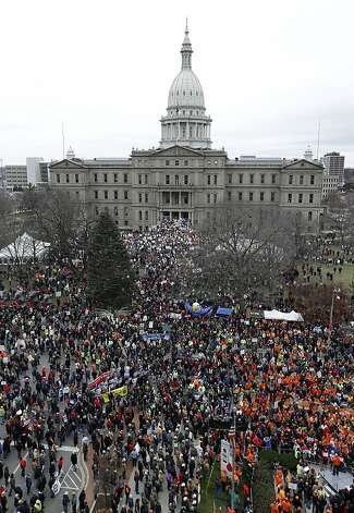 Protesters gather for a rally at the State Capitol in Lansing, Mich., Tuesday, Dec. 11, 2012. The crowd is protesting right-to-work legislation passed last week. Michigan could become the 24th state with a right-to-work law next week. Rules required a five-day wait before the House and Senate vote on each other's bills; lawmakers are scheduled to reconvene Tuesday and Gov. Snyder has pledged to sign the bills into law. (AP Photo/Paul Sancya) Photo: Paul Sancya, Associated Press
