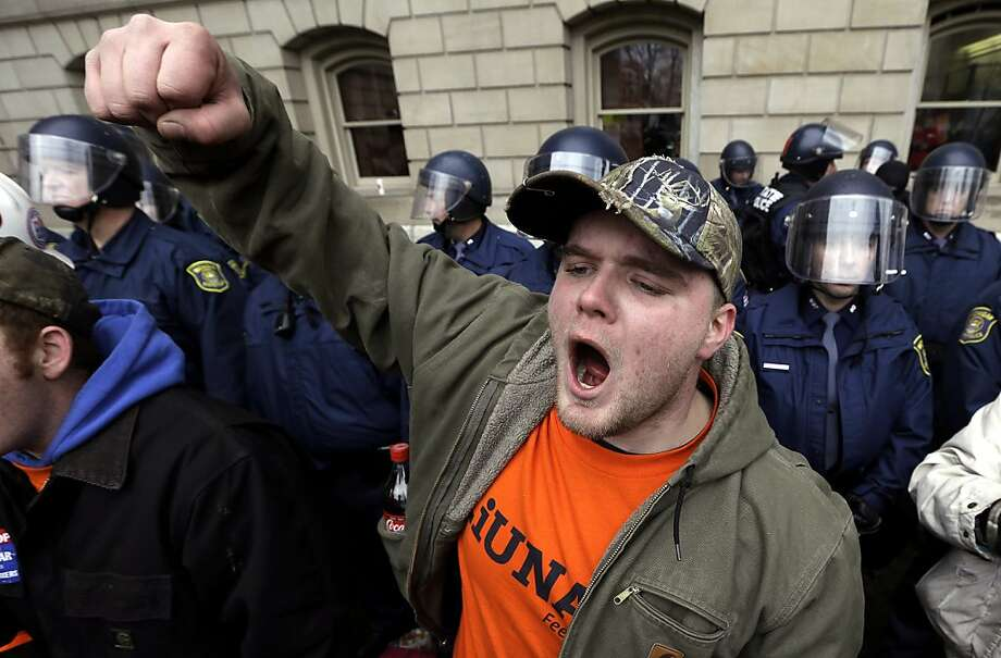 Drew Dobson, of Coleman, Mich., protests at a rally at the State Capitol in Lansing, Mich., Tuesday, Dec. 11, 2012. The crowd is protesting right-to-work legislation passed last week. Michigan could become the 24th state with a right-to-work law next week. Rules required a five-day wait before the House and Senate vote on each other's bills; lawmakers are scheduled to reconvene Tuesday and Gov. Snyder has pledged to sign the bills into law. (AP Photo/Paul Sancya)p Photo: Paul Sancya, Associated Press