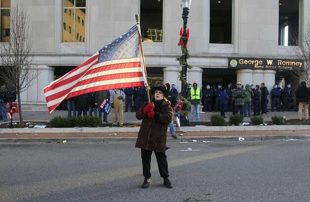 Paula Merwin of Leslie, Mich., waves an American flag outside the George W. Romney State Office Building as lawmakers push final versions of right-to-work legislation in Lansing, Mich., Tuesday, Dec. 11, 2012. The GOP majority has used its superior numbers and backing from Gov. Rick Snyder to speed the legislation through the House and Senate last week, brushing aside denunciations and walkouts by helpless Democrats and cries of outrage from union activists who swarmed the state Capitol hallways and grounds. (AP Photo/Carlos Osorio) Photo: Carlos Osorio, Associated Press