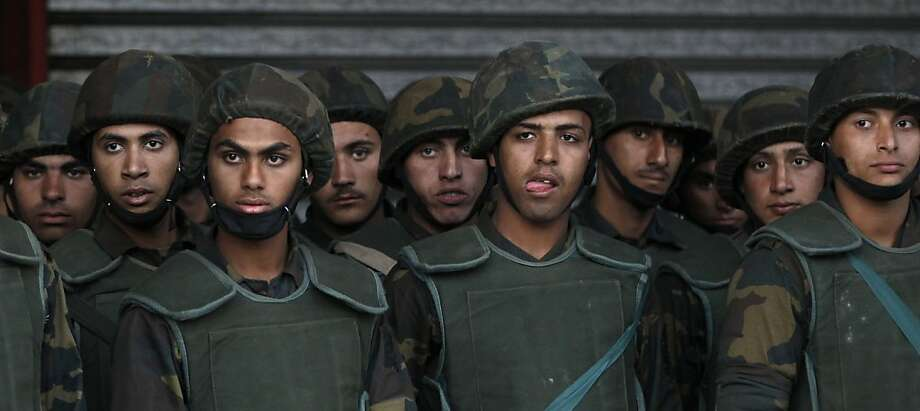 Egyptian army soldiers stand guard during a demonstration in front of the presidential palace in Cairo, Egypt, Tuesday, Dec. 11, 2012. Thousands of opponents and supporters of Egypt's Islamist president were flocking to key locations in the nation's capital ahead of rival mass rallies Tuesday, four days before a nationwide referendum on a contentious draft constitution. (AP Photo/Petr David Josek) Photo: Petr David Josek, Associated Press