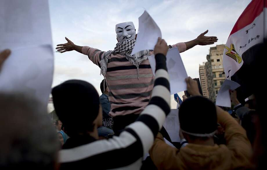 "Protesters opposing Egyptian president Mohammed Morsi, one wearing a Guy Fawkes mask, chant slogans and carry a national flag with Arabic that reads ""January 25,"" during a demonstration in front of el-Nour mosque, background, in Cairo, Egypt, Tuesday, Dec. 11, 2012. Thousands of opponents and supporters of Egypt's Islamist president staged rival rallies in the nation's capital Tuesday, four days ahead a nationwide referendum on a contentious draft constitution.(AP Photo/Nasser Nasser) Photo: Nasser Nasser, Associated Press"
