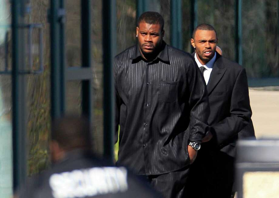 Dallas Cowboys fullback Lawrence Vickers, left, and practice squad member Andre Holmes, right, arrive at Oak Cliff Bible Fellowship for a memorial service for Jerry Brown Tuesday, Dec. 11, 2012, in Dallas. Brown, a member of the team's practice squad was killed early Saturday morning when a car driven by teammate Josh Brent was involved in a single vehicle accident. (AP Photo/LM Otero) Photo: LM Otero, Associated Press / AP