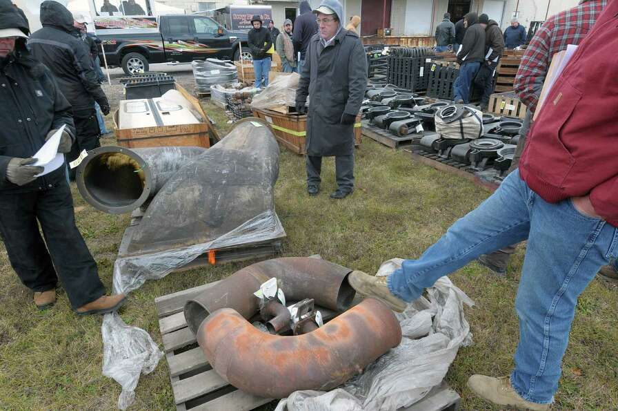 Potential bidders look over items during an auction of State-owned surplus train parts at the Rotter