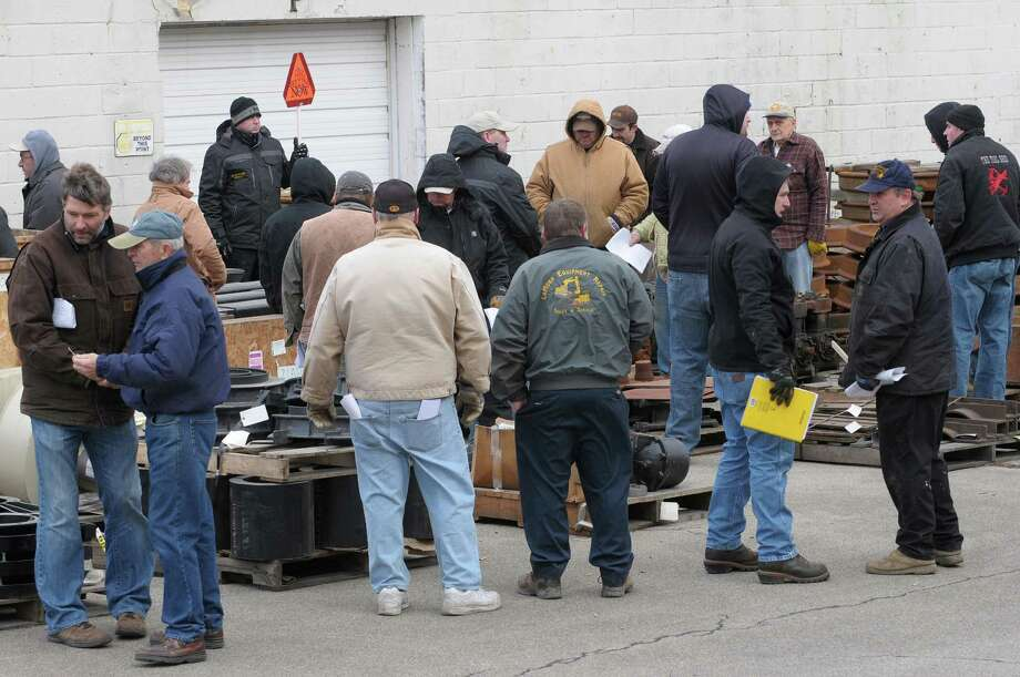 Bidders hover around items as bidding takes place during an auction of State-owned surplus train parts at the Rotterdam Industrial Park on Tuesday, Dec. 11, 2012 in Rotterdam, NY.  (Paul Buckowski / Times Union) Photo: Paul Buckowski