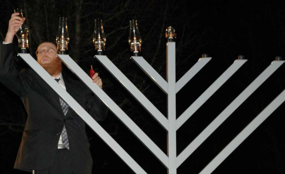 Rabbi Yehuda Kantor on Tuesday night lights what he said is the largest menorah in Westport, Weston or Wilton, celebrating Hanukkah at Chabad of Westport's new home on Wilton Road. Westport CT 12/11/12 Photo: Jarret Liotta / Westport News contributed