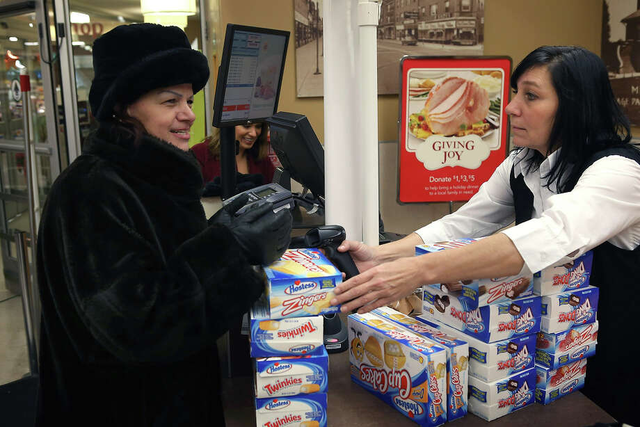 Bini Vedral (R) rings up a Lila Prskalo's purchase of Hostess snacks at a Jewel-Osco grocery store on December 11, 2012 in Chicago, Illinois. The Jewel-Osco grocery store chain purchased the last shipment of 20,000 boxes of Hostess products and put them on sale in their stores throughout the Chicago area today. Hostess Brands Inc. shut down its baking operations and began liquidating assets last month after failing to negotiate a labor contract with Workers with the Bakery, Confectionery, Tobacco Workers and Grain Millers International Union. Photo: Scott Olson, Getty Images / 2012 Getty Images