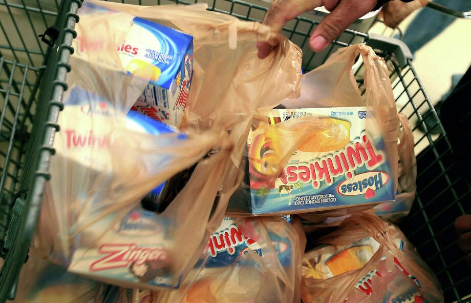 A customer buys boxes of Hostess snacks at a Jewel-Osco grocery store on December 11, 2012 in Chicago, Illinois. The Jewel-Osco grocery store chain purchased the last shipment of 20,000 boxes of Hostess products and put them on sale in their stores throughout the Chicago area today. Hostess Brands Inc. shut down its baking operations and began liquidating assets last month after failing to negotiate a labor contract with Workers with the Bakery, Confectionery, Tobacco Workers and Grain Millers International Union. Photo: Scott Olson, Getty Images / 2012 Getty Images