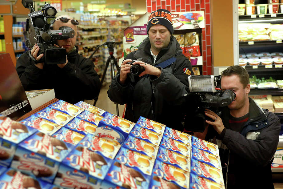 Members of the news media shoot a display of Hostess snacks at a Jewel-Osco grocery store on December 11, 2012 in Chicago, Illinois. The Jewel-Osco grocery store chain purchased the last shipment of 20,000 boxes of Hostess products and put them on sale in their stores throughout the Chicago area today. Hostess Brands Inc. shut down its baking operations and began liquidating assets last month after failing to negotiate a labor contract with Workers with the Bakery, Confectionery, Tobacco Workers and Grain Millers International Union. Photo: Scott Olson, Getty Images / 2012 Getty Images