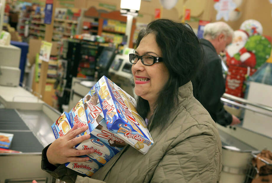 Helen Lumpp heads to the checkout with an armload of Hostess snacks at a Jewel-Osco grocery store on December 11, 2012 in Chicago, Illinois. The Jewel-Osco grocery store chain purchased the last shipment of 20,000 boxes of Hostess products and put them on sale in their stores throughout the Chicago area today. Hostess Brands Inc. shut down its baking operations and began liquidating assets last month after failing to negotiate a labor contract with Workers with the Bakery, Confectionery, Tobacco Workers and Grain Millers International Union. Photo: Scott Olson, Getty Images / 2012 Getty Images