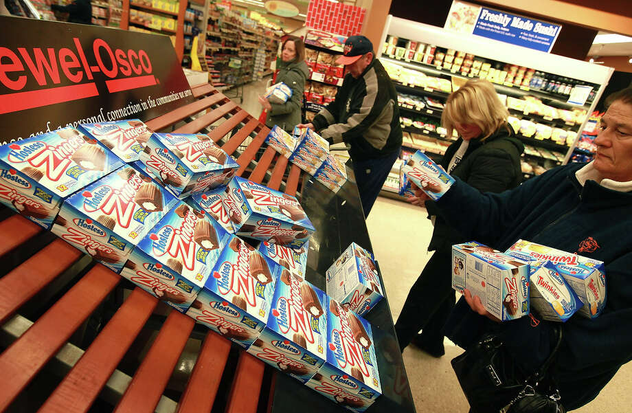 Customers grab up Hostess snacks at a Jewel-Osco grocery store on December 11, 2012 in Chicago, Illinois. The Jewel-Osco grocery store chain purchased the last shipment of 20,000 boxes of Hostess products and put them on sale in their stores throughout the Chicago area today. Hostess Brands Inc. shut down its baking operations and began liquidating assets last month after failing to negotiate a labor contract with Workers with the Bakery, Confectionery, Tobacco Workers and Grain Millers International Union. Photo: Scott Olson, Getty Images / 2012 Getty Images