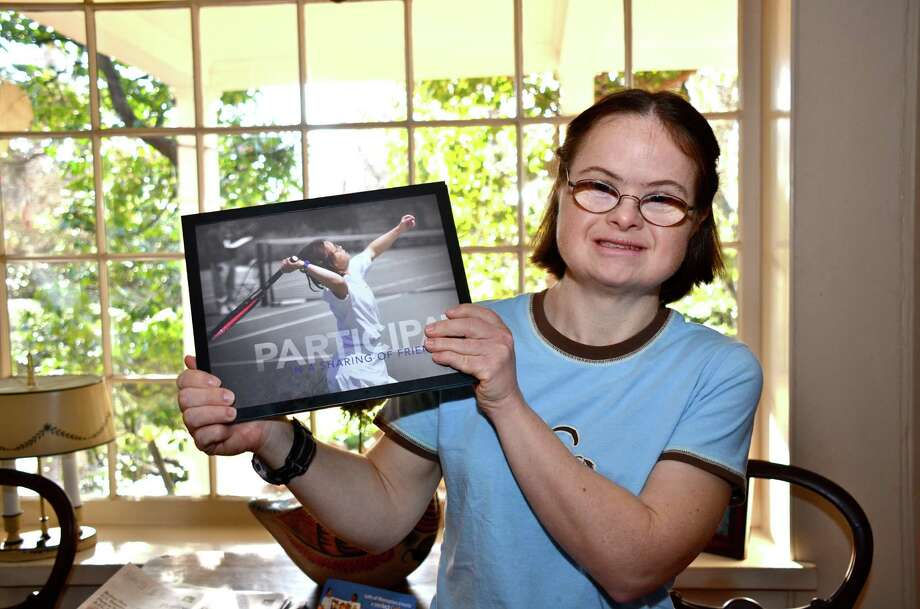 Annie Brautigum proudly holds a photo that a sports photographer took of her during a tennis match last year.  It is one of several mementos and awards that she has accrued over the years for her participation in Special Olympics and other programs.  Dec. 11, 2012, Norwalk, Conn. Photo: Jeanna Petersen Shepard