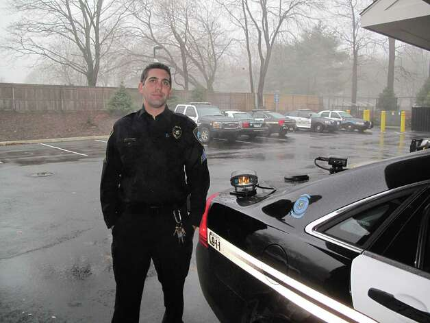 Captain Thomas Moore of the Darien police department stands next to a cruiser equipped with a License Plate Reader (LPR) machine. Dec. 10, 2012. Darien, Conn. Photo: Tyler Woods