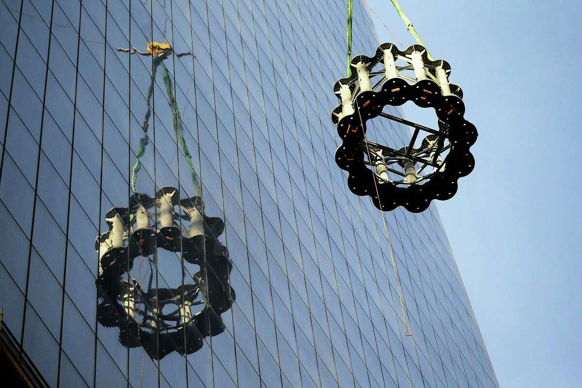 NEW YORK, NY - DECEMBER 12: The first piece of the spire is hoisted atop One World Trade Center on December 12, 2012 in New York City. The first of 18 sections of spire was hoisted atop the 104-story building by crane this morning.