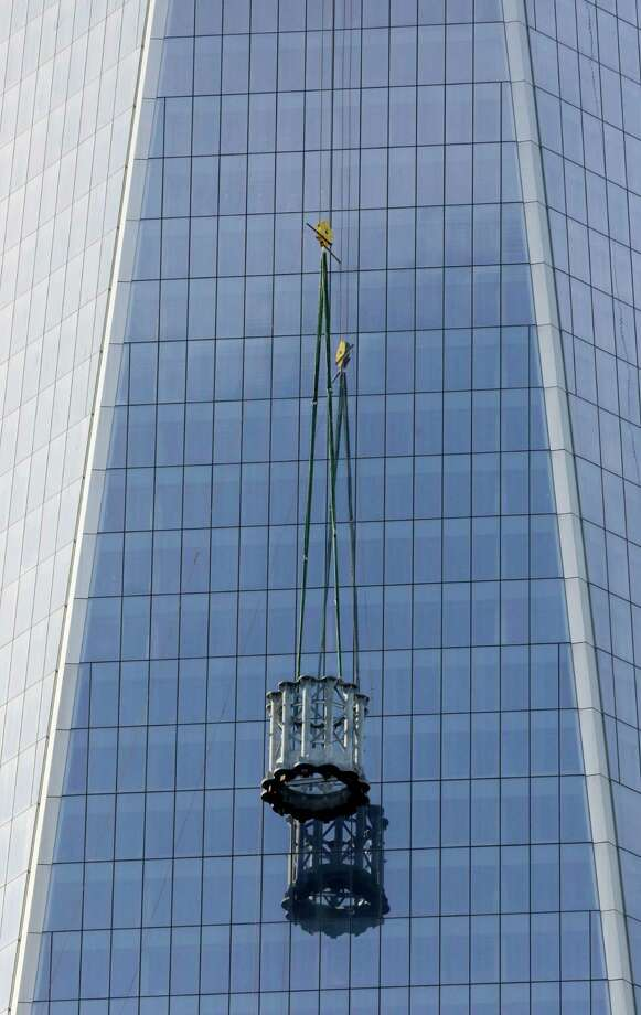The first section of a 408-foot spire is hoisted by crane to the top of One World Trade Center, Wednesday, Dec. 12, 2012 in New York. The spire will be fully assembled in 2013 and the tower will top out at 1776 feet. Photo: Mark Lennihan, AP / AP