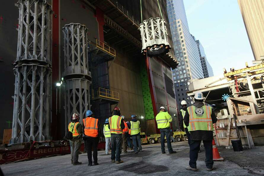 NEW YORK, NY - DECEMBER 12:  Workers  watch as the first piece of the spire is hoisted atop One Worl