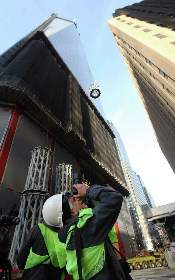 NEW YORK, NY - DECEMBER 12:  A photographer takes pictures as the first piece of the spire is hoisted atop One World Trade Center on December 12, 2012 in New York City.  The first of 18 sections of spire was hoisted atop the 104-story building by crane this morning. Photo: Mario Tama, Getty Images / 2012 Getty Images