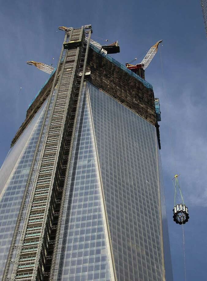 NEW YORK, NY - DECEMBER 12: The first piece of the spire is hoisted atop One World Trade Center on December 12, 2012 in New York City.  The first of 18 sections of spire was hoisted atop the 104-story building by crane this morning. Photo: Mario Tama, Getty Images / 2012 Getty Images