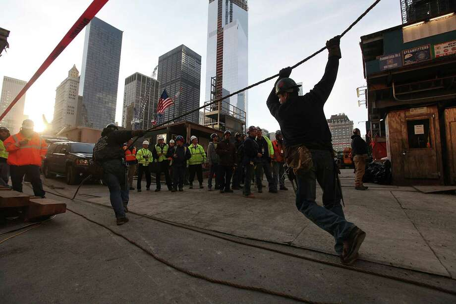 NEW YORK, NY - DECEMBER 12:  Workers pull a rope as they prepare the first piece of the spire to be hoisted atop One World Trade Center on December 12, 2012 in New York City.  The first of 18 sections of spire was hoisted atop the 104-story building by crane this morning. Photo: Mario Tama, Getty Images / 2012 Getty Images