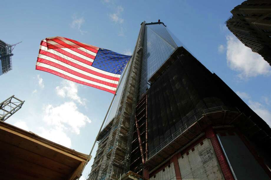 An American flag flies next to One World Trade Center, Tuesday, Dec. 11, 2012 in New York.  A 408-foot spire is expected to rise on top of the tower into the Manhattan sky by spring. Photo: Mark Lennihan, AP / AP