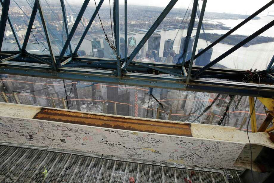 A steel beam, bearing the signatures of hundreds of workers and President Barack Obama, is in place on the 104th floor of One World Trade Center, Tuesday, Dec. 11, 2012 in New York.  A 408-foot spire is expected to rise on top of the tower by spring. Photo: Mark Lennihan, AP / AP