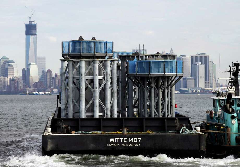 A barge loaded with sections of spire for One World Trade Center, left, is guided by tugboat across New York Harbor, Tuesday, Dec. 11, 2012 in New York. Photo: Mark Lennihan, AP / AP