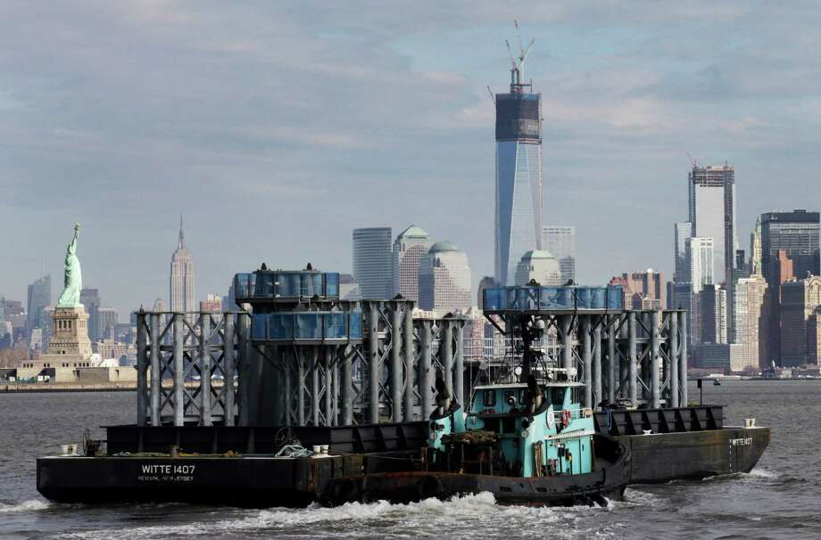 A barge loaded with sections of spire for One World Trade Center, center, is guided by tugboat across New York Harbor, Tuesday, Dec. 11, 2012 in New York. The Statue of Liberty is at left, and the Empire State Building is second left. Photo: Mark Lennihan, AP / AP