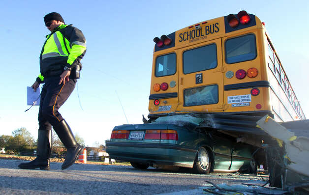 A police officer walks around the scene of a fatal bus accident  Wednesday, Dec. 12, 2012, in Hockley. Photo: Cody Duty, Associated Press / Houston Chronicle