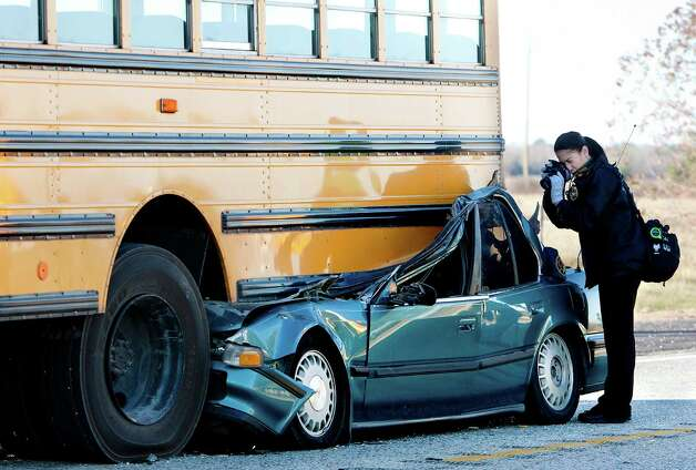 An investigator photographs the aftermath of a fatal bus accident Wednesday, Dec. 12, 2012, in Hockley. Photo: Cody Duty, Associated Press / Houston Chronicle