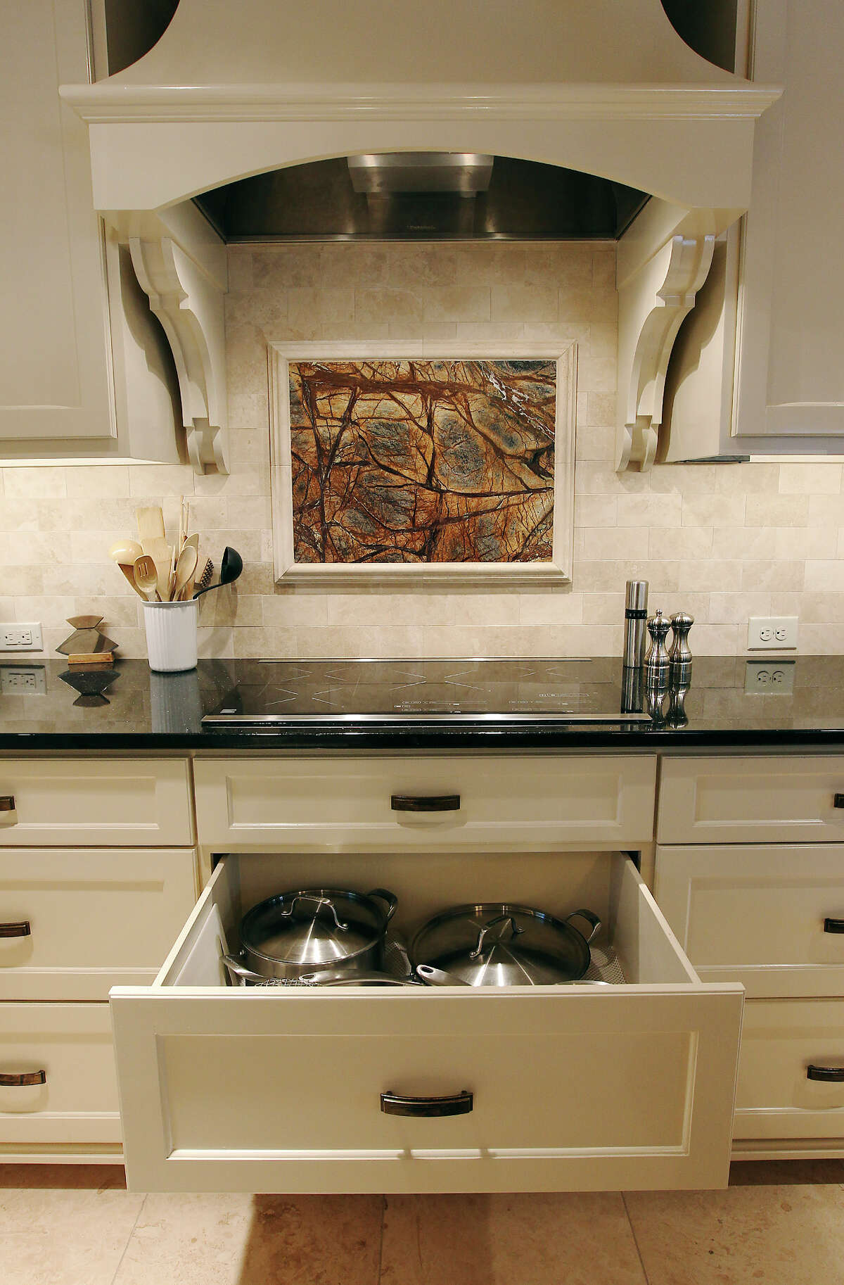 Linda and Bill Blanton's newly remodeled kitchen in Pleasanton, Texas on Tuesday, Nov. 27, 2012. Under the electric range top are drawers for the Blantons to store pots and pans. On the back splash is a granite insert that matches the kitchen island.