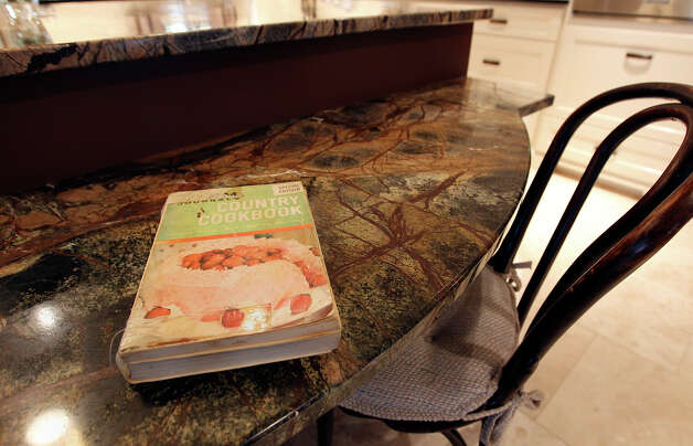 Linda and Bill Blanton's newly remodeled kitchen in Pleasanton, Texas on Tuesday, Nov. 27, 2012. A well-worn recipe book used often by the culinary couple is seen on the island's stepped counter top. Photo: Kin Man Hui, San Antonio Express-News / © 2012 San Antonio Express-News