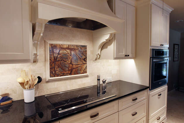 Linda and Bill Blanton's newly remodeled kitchen in Pleasanton, Texas on Tuesday, Nov. 27, 2012. Another view of the electric range top featuring a granite insert on the back splash. Photo: Kin Man Hui, San Antonio Express-News / © 2012 San Antonio Express-News