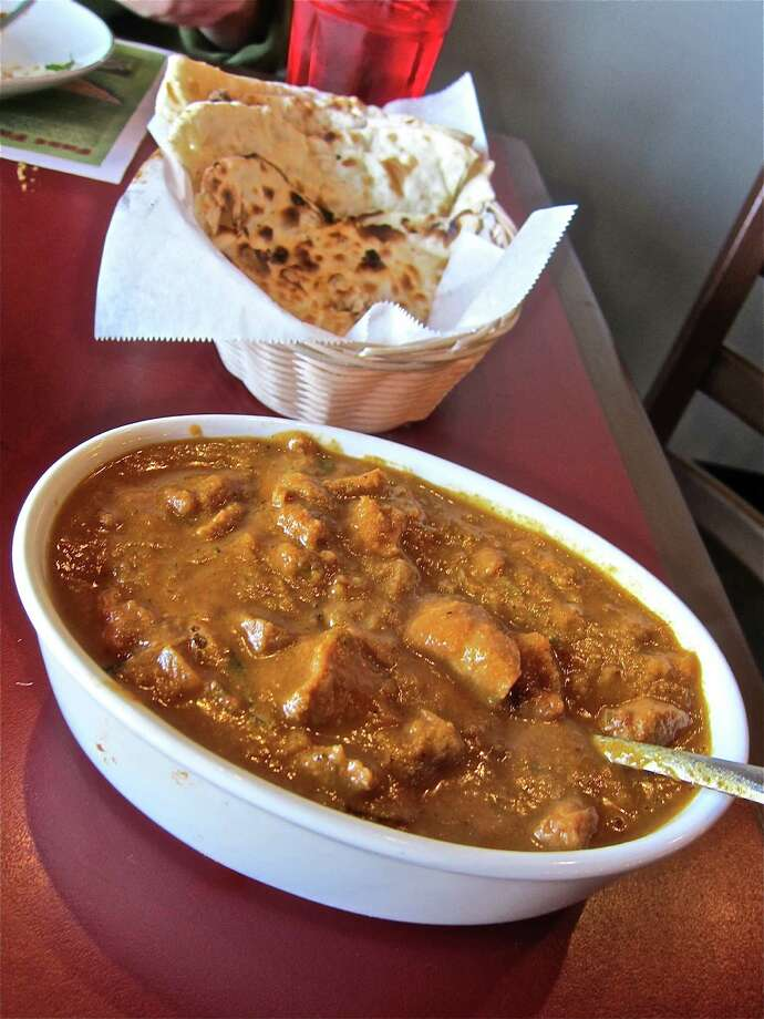 The Hyderabadi Vegetable Dum Biryani at Biryani Pot, located on 6509 Westheimer, arrived with a cooling raita and a warming mirchi ka salan sauce, left, while the Hyderabadi Murg Masala, a chicken curry with a ground-sesame-and-onion base, delivered a welcomed spiciness. Photo: Alison Cook
