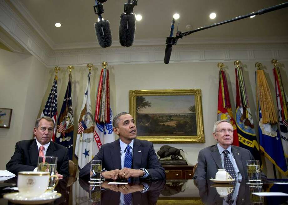 President Barack Obama, flanked by House Speaker John Boehner of Ohio, left, and Senate Majority Leader Harry Reid of Nev., speaks to reporters in the Roosevelt Room of the White House in Washington, Friday Nov. 16.  (Carolyn Kaster / AP Photo)