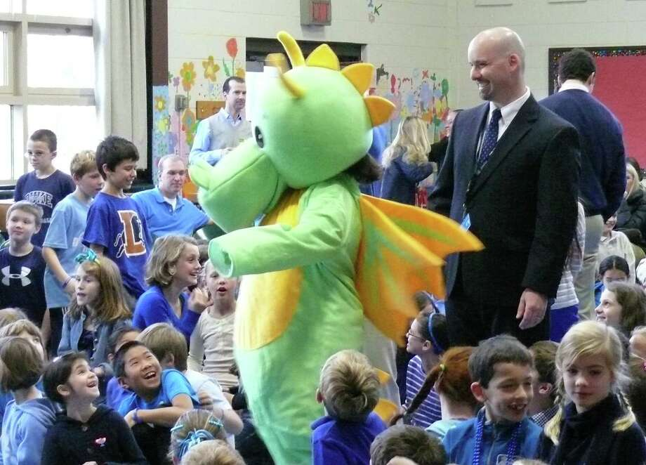 Dwight the Dragon and Principal Scott Bannon kick off the ceremony Wednesday honoring the school's selected as a National Blue Ribbon School. Photo: Genevieve Reilly / Fairfield Citizen