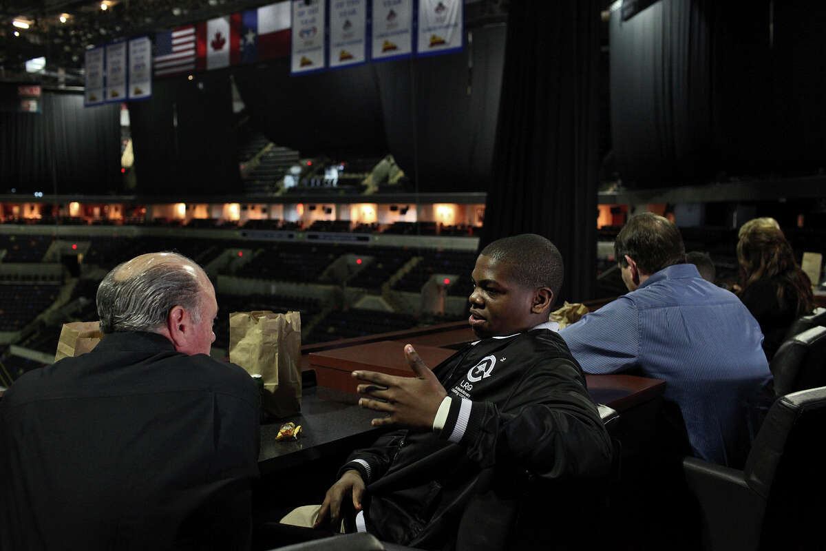 Marlon Springs, 13, right, talks with Frank Miceli, left, Senior Vice President of Sales and Marketing with the San Antonio Spurs, during lunch with Big Brothers Big Sisters of South Texas at the AT&T Center in San Antonio on Nov. 27, 2012.