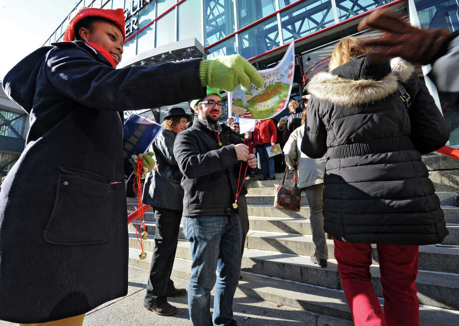 UAlbany students and Downtown Albany BID interns Annette Dunlap, left, and Alex Gordon pass out lyric sheets and jingle bells to people who are arriving to participate in setting the world record for being the largest group singing jingle bells while ringing jingle bells for recordsetter.com in front of the Times Union Center on Wednesday Dec. 12, 2012 at 12 Noon in Albany, N.Y.  (Lori Van Buren / Times Union) Photo: Lori Van Buren