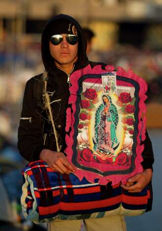 Pilgrim Juan Perez, 20, from Cholula, poses with his image of the Virgin of Guadalupe outside the Basilica of Guadalupe, in Mexico City, Wednesday, Dec. 12, 2012. Hundreds of thousands of people from all over the country converge on Mexico's holy Roman Catholic site, many bringing with them images or statues of Mexico's patron saint to be blessed, marking the Virgin's Dec. 12 feast day. (AP Photo/Eduardo Verdugo) Photo: Eduardo Verdugo, Associated Press / AP