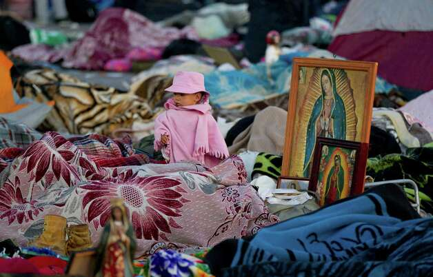 A child stands amid a mass of sleeping pilgrims next to images of the Virgin of Guadalupe on the plaza of the Basilica of Guadalupe, in Mexico City, Wednesday, Dec. 12, 2012. Hundreds of thousands of people from all over the country converge on Mexico's holy Roman Catholic site, many bringing with them images or statues of Mexico's patron saint to be blessed, marking the Virgin's Dec. 12 feast day. (AP Photo/Eduardo Verdugo) Photo: Eduardo Verdugo, Associated Press / AP