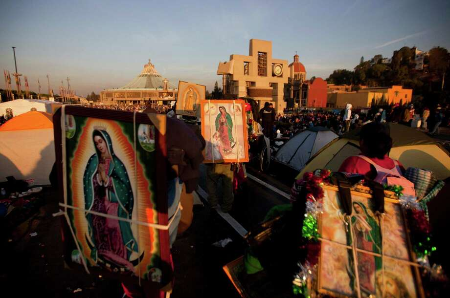 Pilgrims carry on their backs images of the Virgin of Guadalupe towards the Basilica of Guadalupe, in Mexico City, Wednesday, Dec. 12, 2012. Hundreds of thousands of people from all over the country converge on Mexico's holy Roman Catholic site, many bringing with them images or statues of Mexico's patron saint to be blessed, marking the Virgin's Dec. 12 feast day. (AP Photo/Eduardo Verdugo) Photo: Eduardo Verdugo, Associated Press / AP
