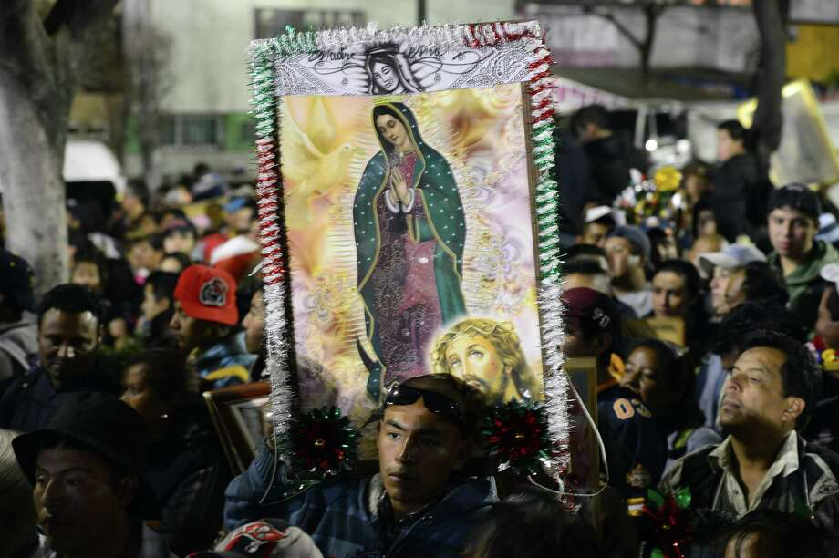 Pilgrims hold an image of Guadalupe Virgin before the birthday of the Guadalupe Virgin at the Basilica de Guadalupe in Mexico City on December 11, 2012. Mexicans celebrated the appearance of the Virgin of Guadalupe to Juan Diego in 1531.    AFP PHOTO/Alfredo EstrellaALFREDO ESTRELLA/AFP/Getty Images Photo: ALFREDO ESTRELLA, AFP/Getty Images / ALFREDO ESTRELLA