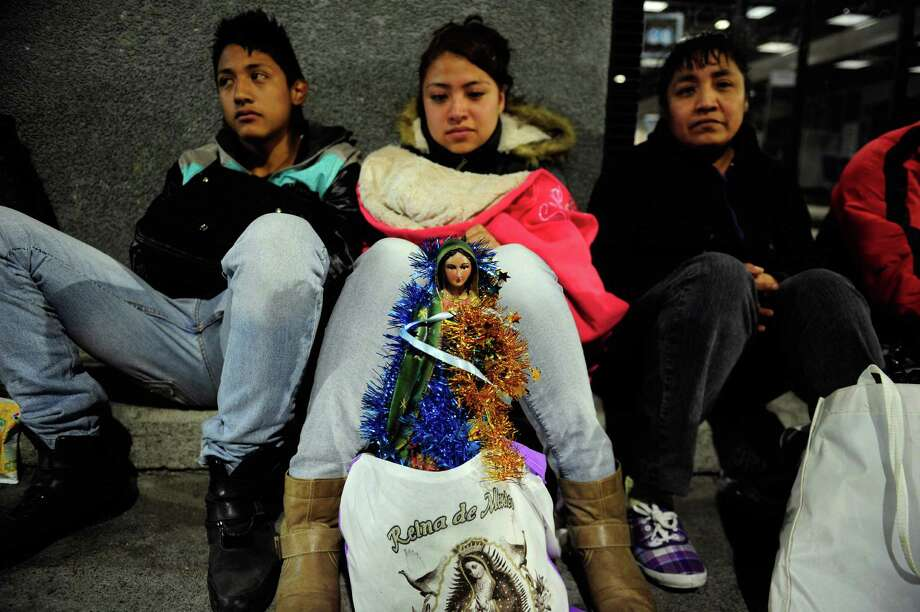 Pilgrims sit with an image of the Guadalupe Virgin near the Basilica de Guadalupe in Mexico City on December 11, 2012.  Mexicans celebrated the appearance of the Virgin of Guadalupe to Juan Diego in 1531.    AFP PHOTO/Alfredo EstrellaALFREDO ESTRELLA/AFP/Getty Images Photo: ALFREDO ESTRELLA, AFP/Getty Images / ALFREDO ESTRELLA