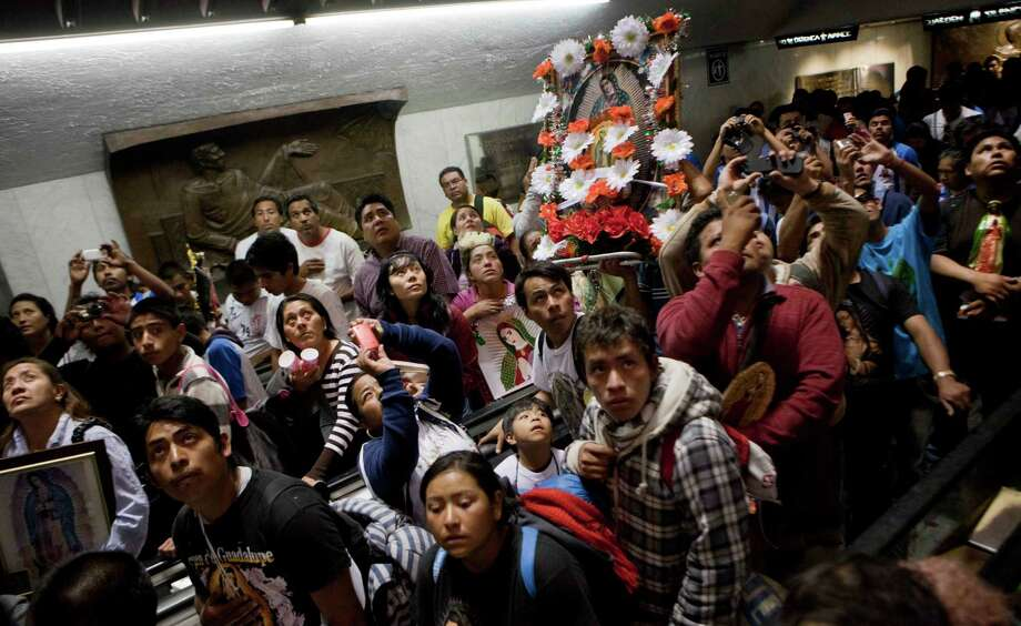 People carrying images of the Virgin of Guadalujpe look up at the original image of her inside the Basilica of Guadalupe in Mexico City, Tuesday Dec. 11, 2012.  Nationwide, devotees of the Virgin of Guadalupe make a pilgrimage to the basilica with images of her to be blessed in honor of her Dec. 12 feast day. (AP Photo/Eduardo Verdugo) Photo: Eduardo Verdugo, Associated Press / AP