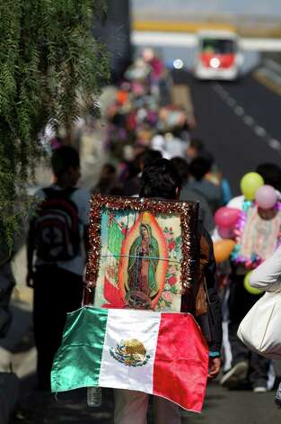 A pilgrim carries a statue of the Virgin of Guadalupe on his back as he makes his way with other pilgrims toward the Basilica of Guadalupe along a highway entering Mexico City, Tuesday, Dec. 11. 2012.  Nationwide, devotees of the Virgin of Guadalupe make a pilgrimage to the basilica with images of her to be blessed in honor of her Dec. 12 feast day. (AP Photo/Eduardo Verdugo) Photo: Eduardo Verdugo, Associated Press / AP