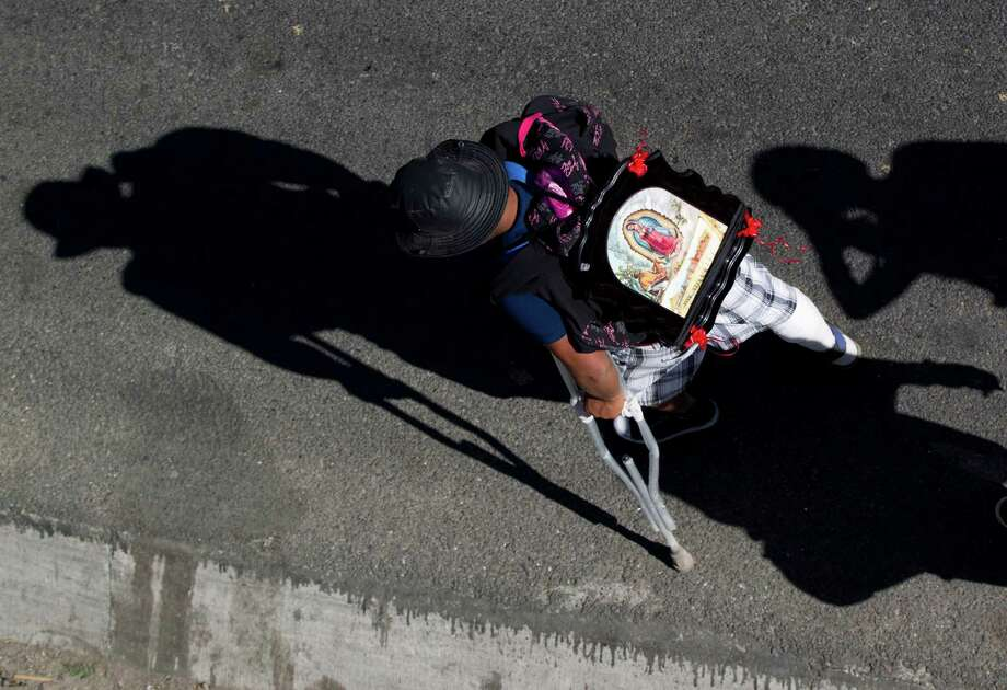 A man using crutches carries an image of the Virgin of Guadalupe on his back as he walks along a highway entering the capital during his pilgrimage to the Basilica of Guadalupe, Tuesday Dec. 11. 2012. Nationwide, devotees of the Virgin of Guadalupe make a pilgrimage to the Basilica in honor of her Dec. 12 feast day. (AP Photo/Eduardo Verdugo) Photo: Eduardo Verdugo, Associated Press / AP