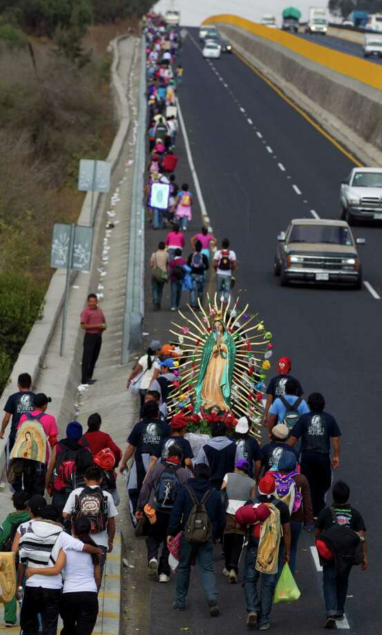 Pilgrims carry a statue of the Virgin of Guadalupe as they walk along the shoulder of a highway toward the Basilica of Guadalupe at the entrance to Mexico City, Tuesday, Dec. 11. 2012.  Nationwide, devotees of the Virgin of Guadalupe make a pilgrimage to the basilica with images of her to be blessed on her Dec. 12 feast day. (AP Photo/Eduardo Verdugo) Photo: Eduardo Verdugo, Associated Press / AP