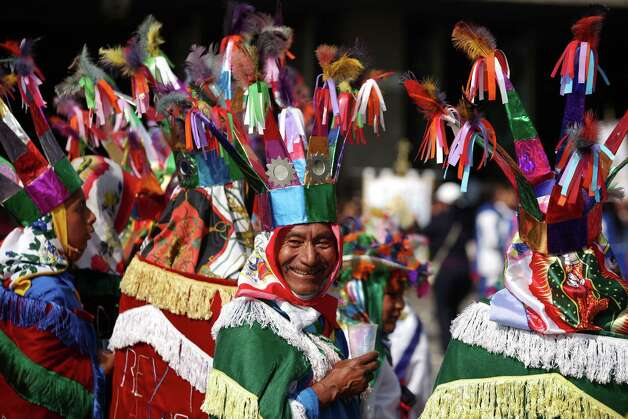 "Francisco Castillo, 62, part of a group of pilgrims from Puebla state performing the ""Danza de los Negritos"" smiles while taking a break during the festivities of the Virgin of Guadalupe at the Basilica of Guadalupe  in Mexico City, Tuesday Dec. 11, 2012. Nationwide, devotees of the Virgin of Guadalupe make a pilgrimage to the basilica in honor of her Dec. 12 feast day. (AP Photo/Denisse Pohls) Photo: Denisse Pohls, Associated Press / AP"