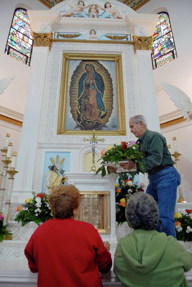 Pablo Gonzalez  lifted an arrangement of fresh cut flowers to an area under a painting of the Virgen of Guadalupe in the Virgen de Guadalupe church in Brownsville, Texas, where preparations were underway, Tuesday, Dec. 11, 2012 for the annual Guadalupana. (AP Photo/The Brownsville Herald, Brad Doherty) Photo: Brad Doherty, Associated Press / The Brownsville Herald