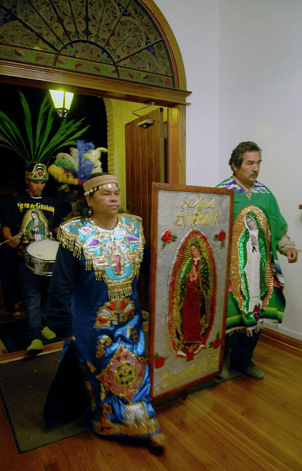 Rosa Linda Alvarado and her husband Jesus de Jesus Alvarado  carry a sign bearing the image of the Virgin de Guadalupe  into a church in Brownsville, Texas Wednesday, Dec. 12, 2012 during a celebration of Virgin of Guadalupe's feast day, Wednesday, Dec. 12, 2012. (AP Photo/The Brownsville Herald, Brad Doherty) Photo: Brad Doherty, Associated Press / BROWNSVILLE HERALD