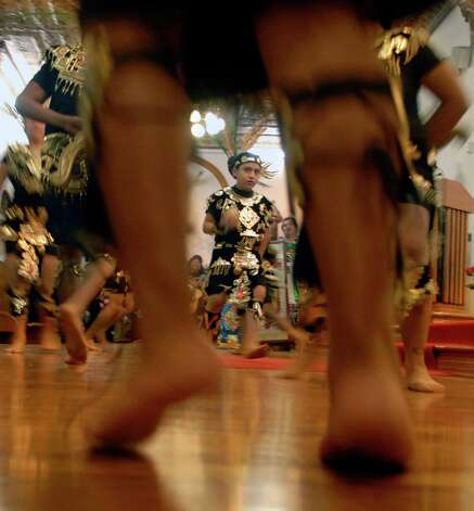 Local dancers dressed in traditional clothing take their turns dancing as they entered the Virgin of Guadalupe church in Brownsville, Texas, during a celebration of Virgin of Guadalupe's feast day, Wednesday, Dec. 12, 2012. (AP Photo/The Brownsville Herald, Brad Doherty) Photo: Brad Doherty, Associated Press / BROWNSVILLE HERALD