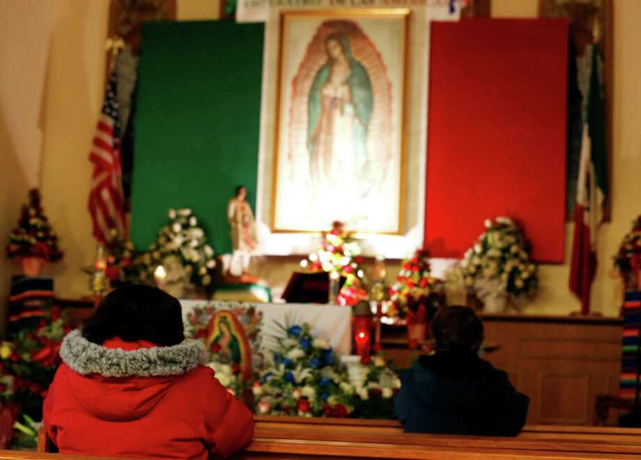 Worshipers pray at the Our Lady of Fatima  Church in front of image of Virgin of Guadalupe during the virgin's feast day, Wednesday, Dec. 12, 2012, in Passaic, N.J. Catholic Mexicans living in New Jersey pay homage to the Virgin on Dec. 12, to observe what they believe was an apparition of the Virgin seen by Juan Diego, an indigenous man, on the hill of Tepeyac in Mexico City on Dec. 12, 1531. (AP Photo/Julio Cortez) Photo: Julio Cortez, Associated Press / AP